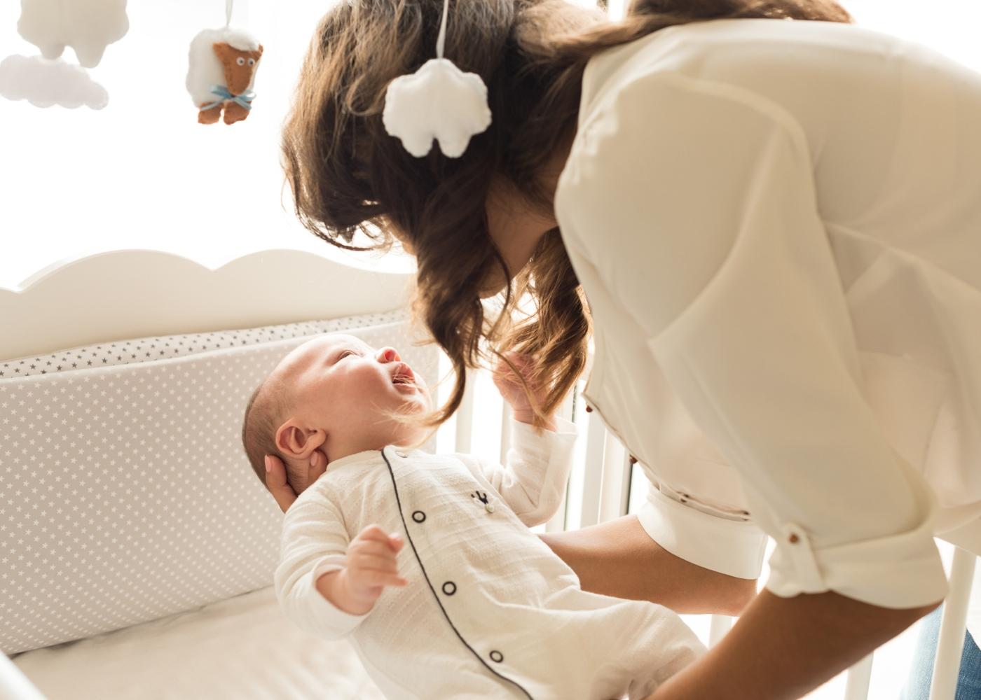 Mãe a deitar bebé no berço