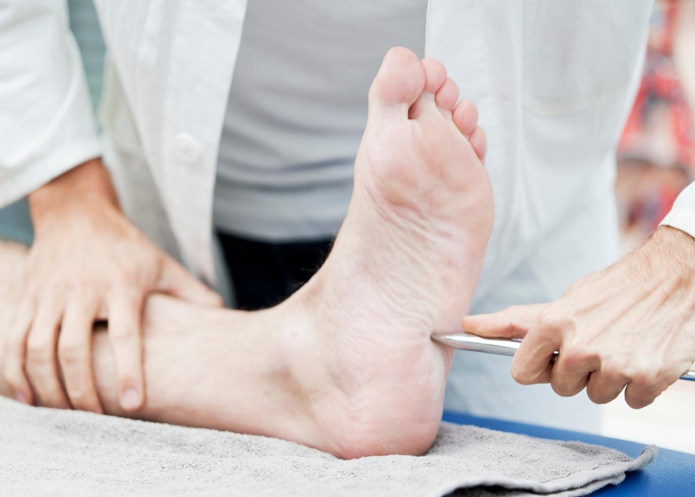 Médico a analisar sensibilidade ao toque nos pés de paciente