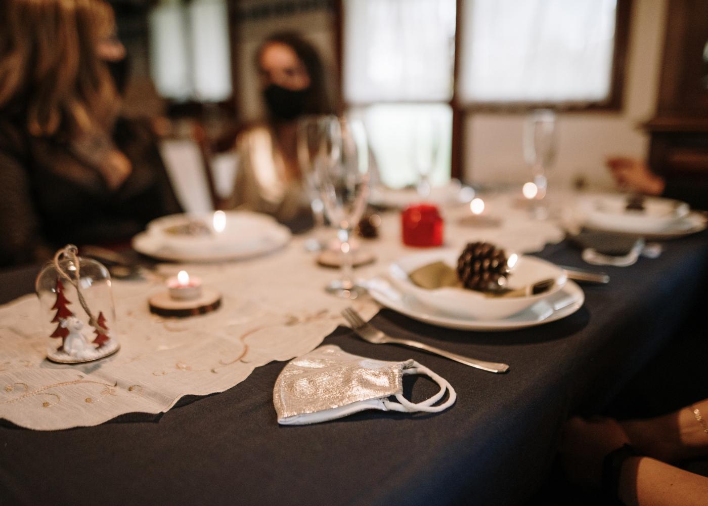 Pessoas sentadas à mesa da consoada de Natal com máscara