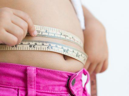 Menina obesa a medir a cintura com uma fita métrica
