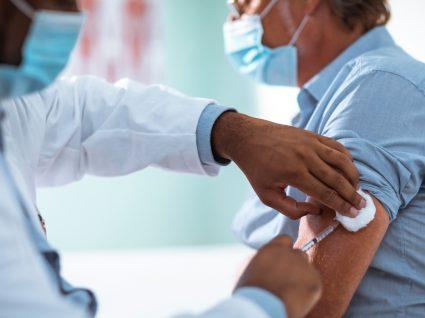 Médico a vacinar utente contra a COVID-19