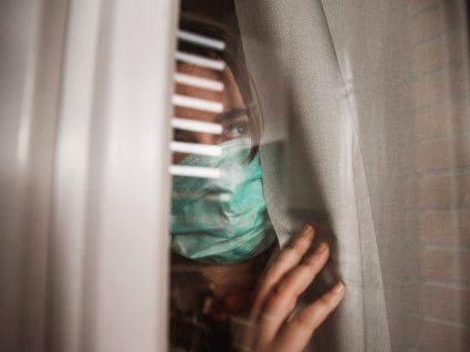 Mulher com máscara a espreitar pela janela