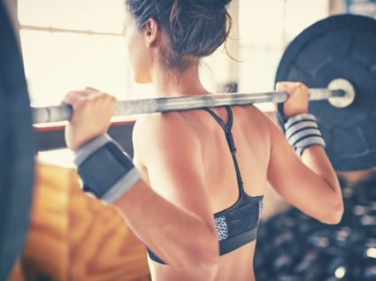 Mulher no ginásio a trabalhar o princípio da sobrecarga progressiva