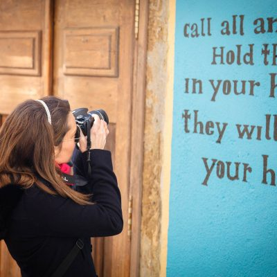 senhora a tirar fotografia a parede da rua