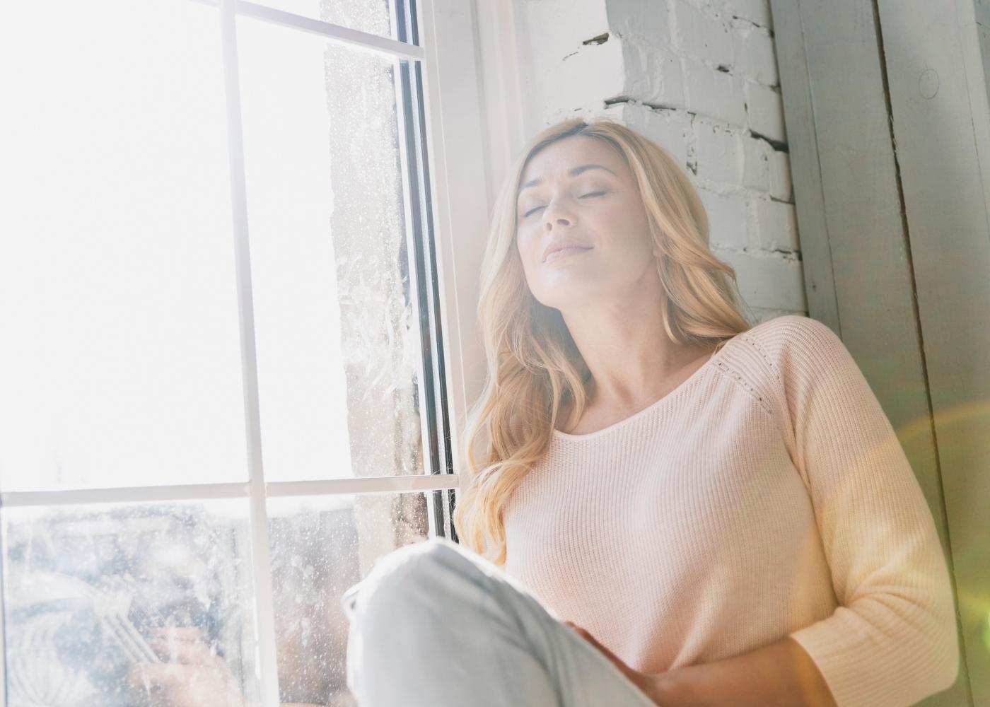 Mulher na janela a apanhar sol e com sentimento de esperança em relação ao futuro