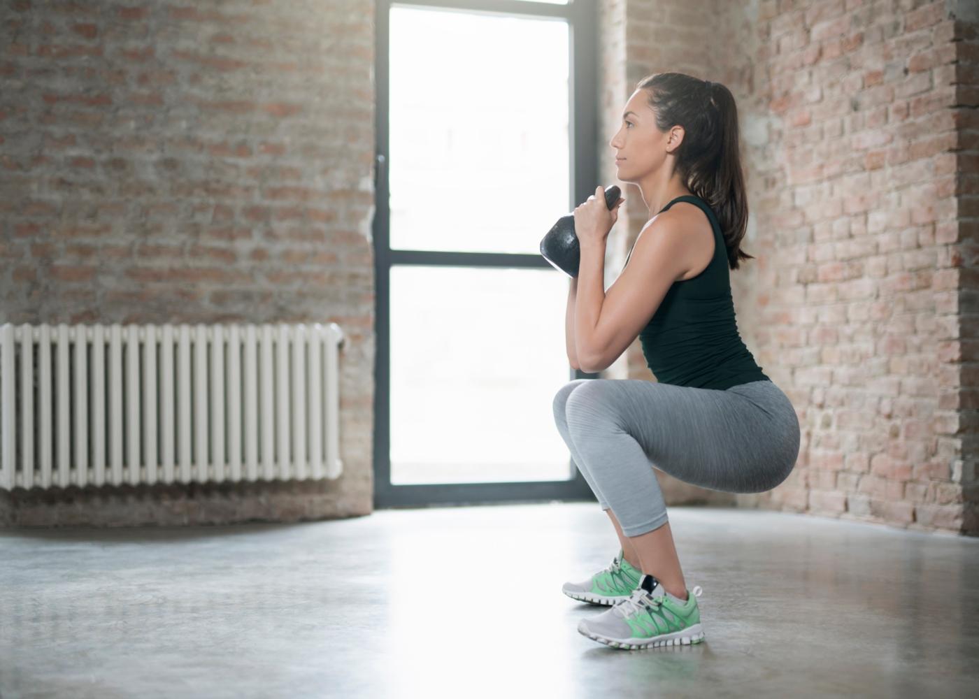 Mulher a fazer agachamento com peso