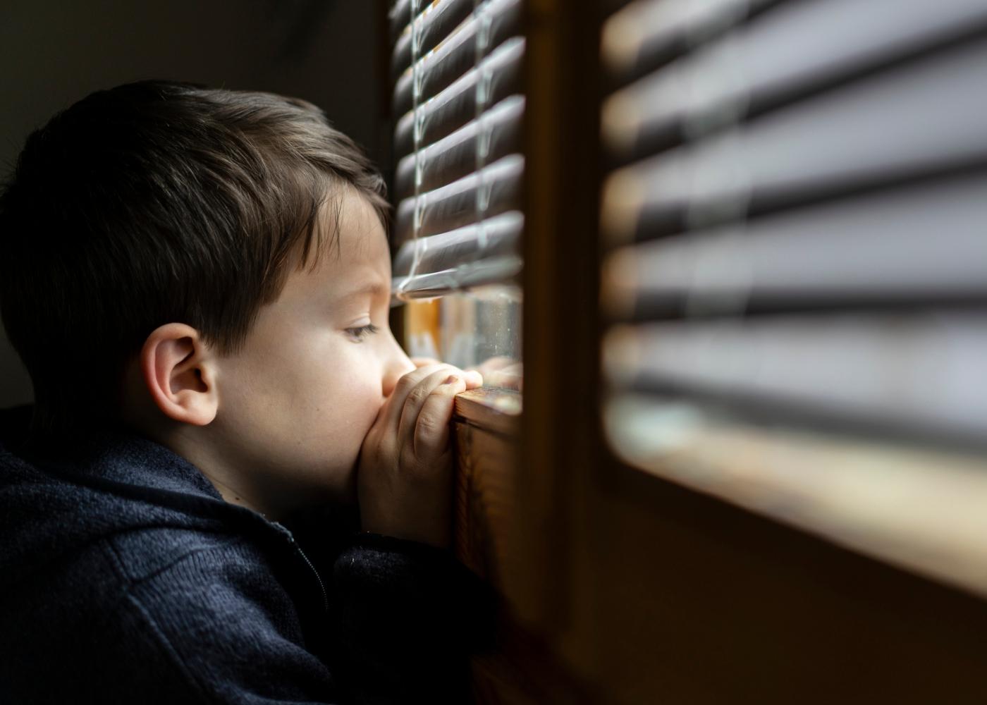 Menino em casa a espreitar pela janela