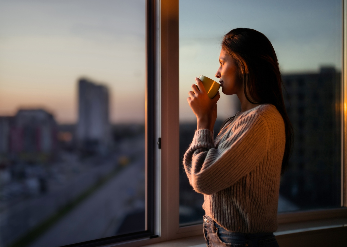 Mulher a olhar para o horizonte a partir da janela de casa