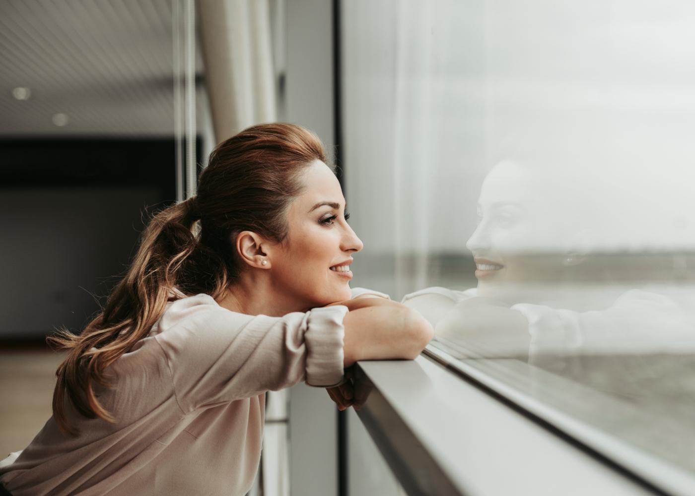 Mulher a contemplar a paisagem pela janela de casa