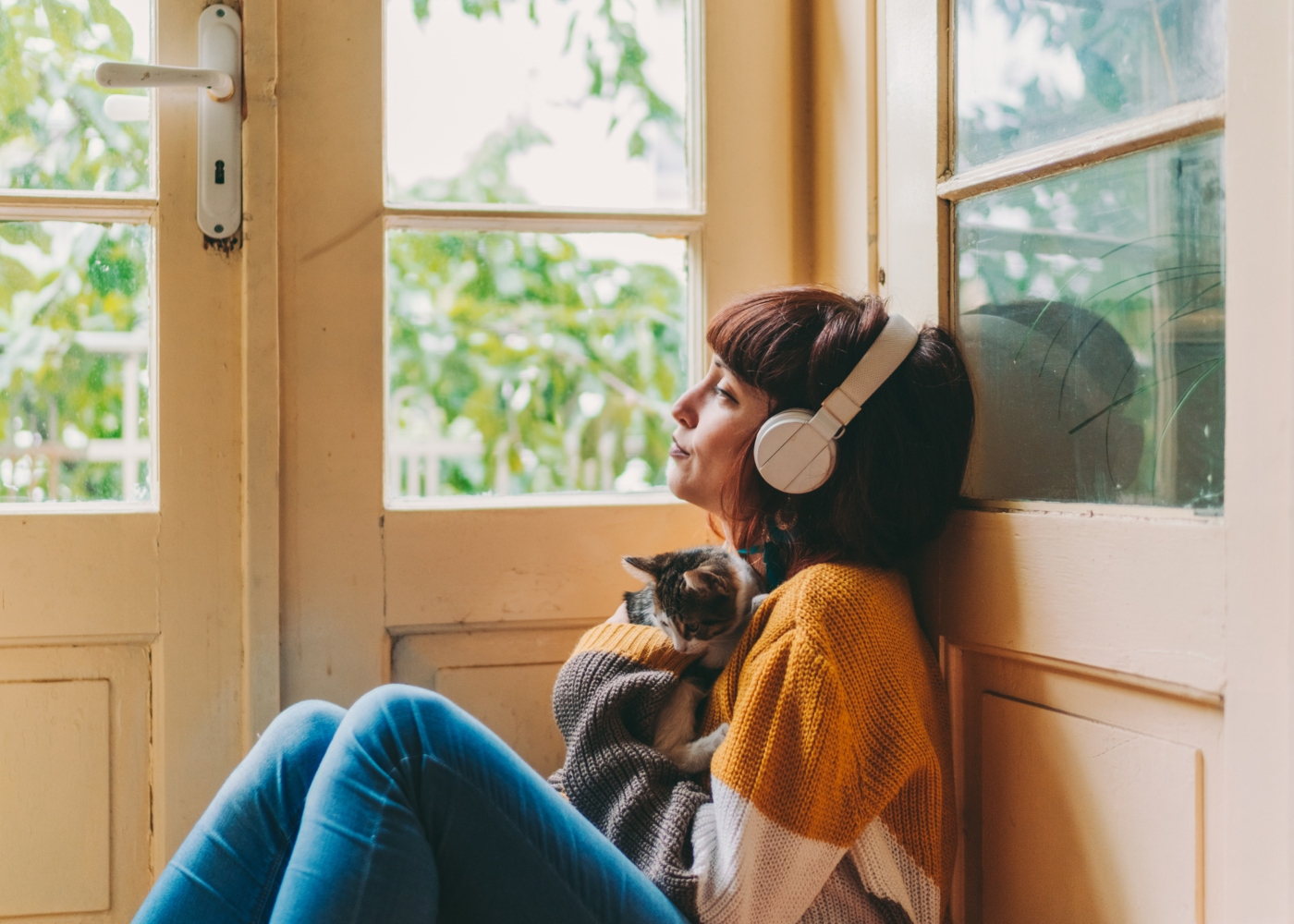 Mulher a ouvir música em casa com um gato ao colo