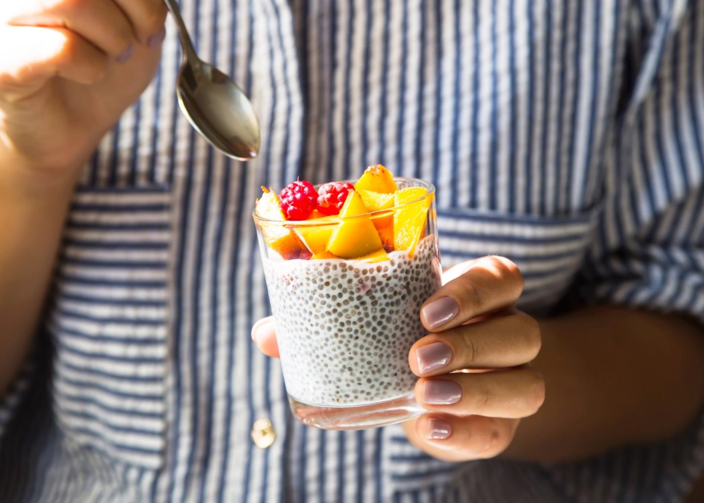 Mulher a comer pudim de chia com fruta