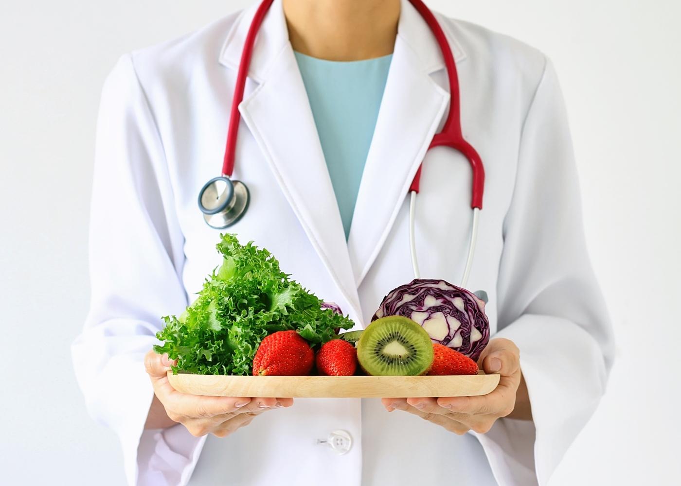 Médico a segurar tabuleiro com frutas e legumes
