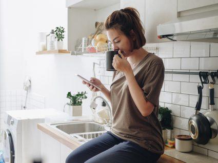 Mulher a fazer scroll passivo nas redes sociais enquanto bebe chá