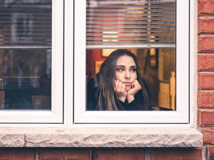 Mulher confinada em casa a olhar pela janela