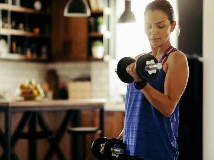 Mulher a preparar-se para fazer um treino completo com halteres em casa