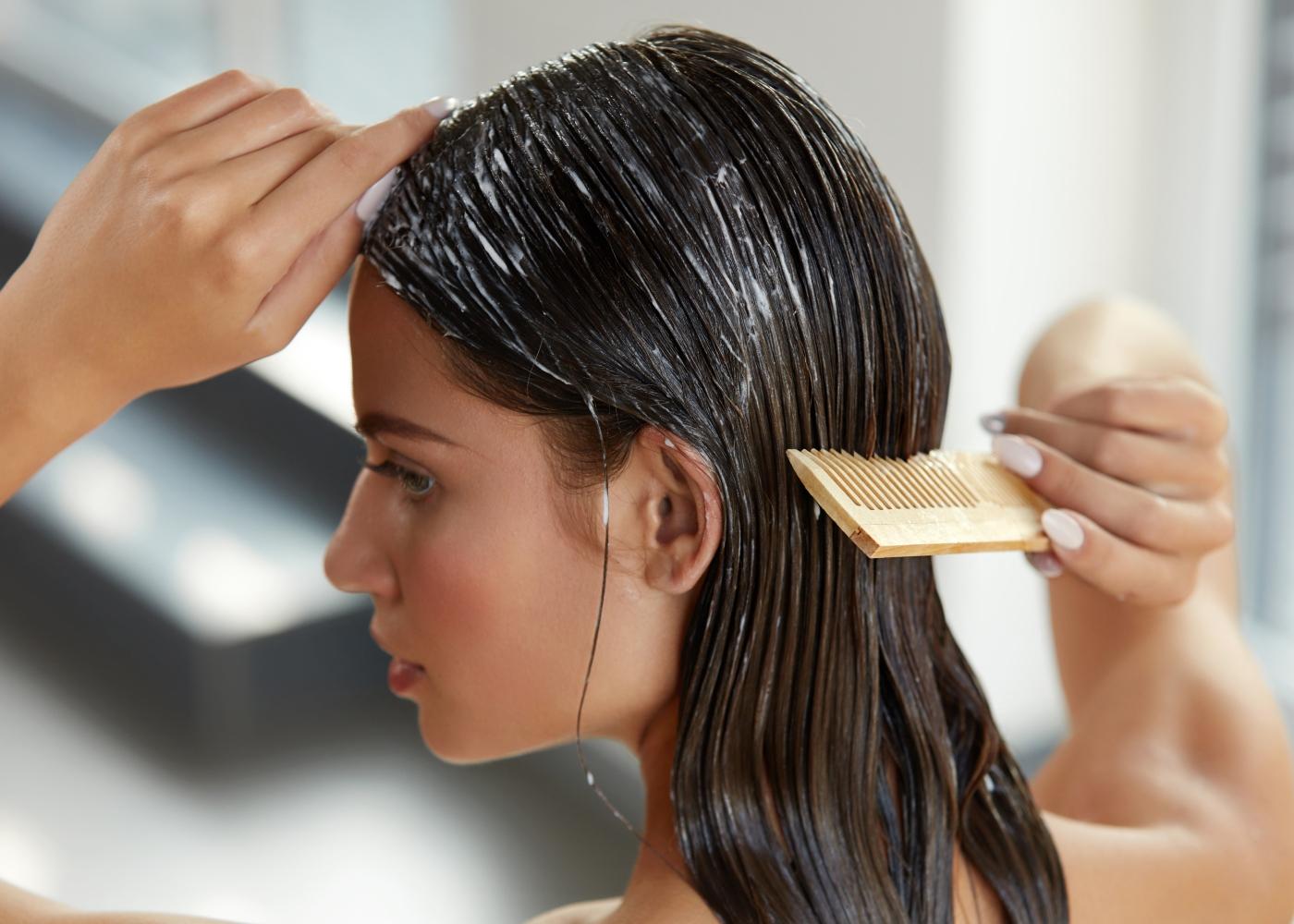 Mulher a aplicar máscara de cabelo caseira