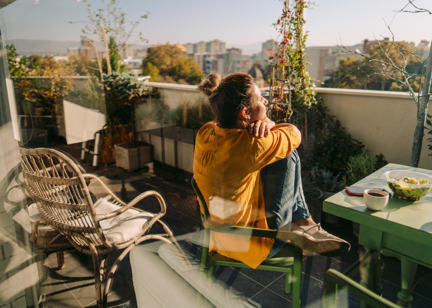 Mulher a almoçar na varanda de casa