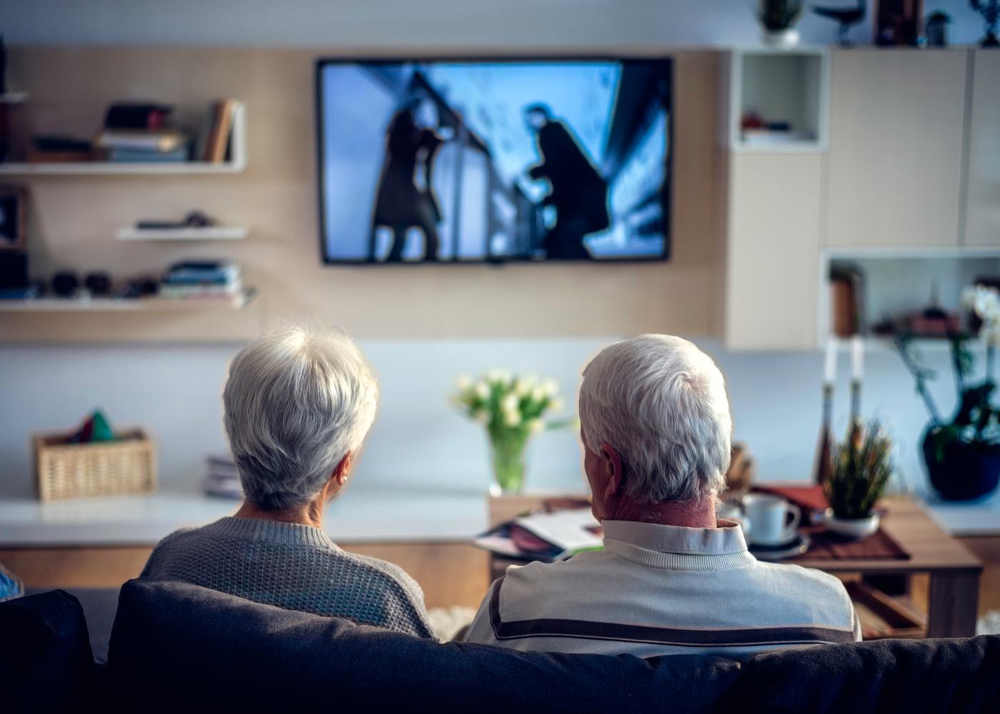 Casal de idosos em casa a ver televisão