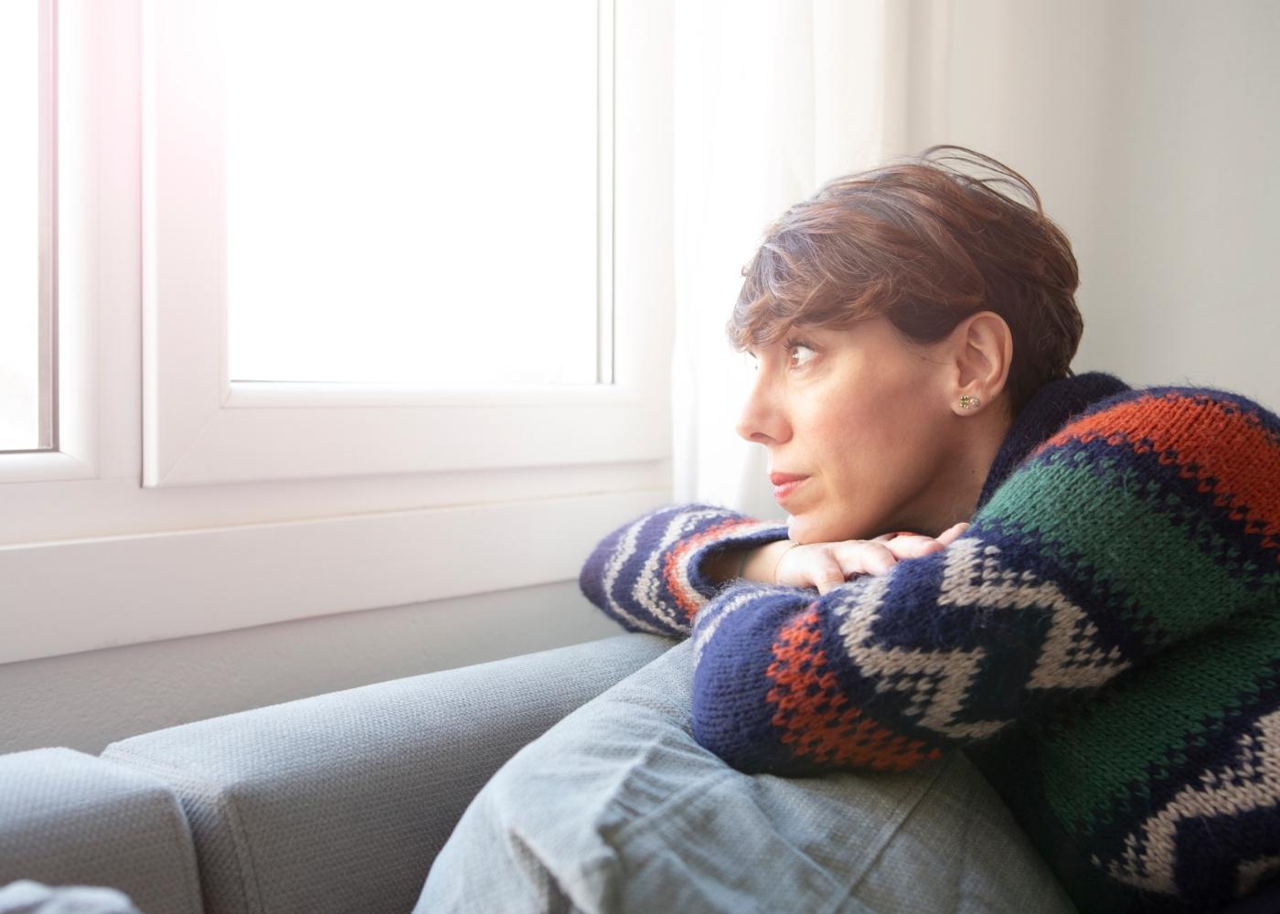Mulher de meia idade sentada no sofá a olhar pela janela