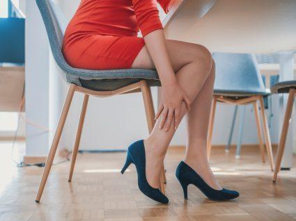 Mulher sentada numa cadeira com dores causadas pela má circulação nas pernas