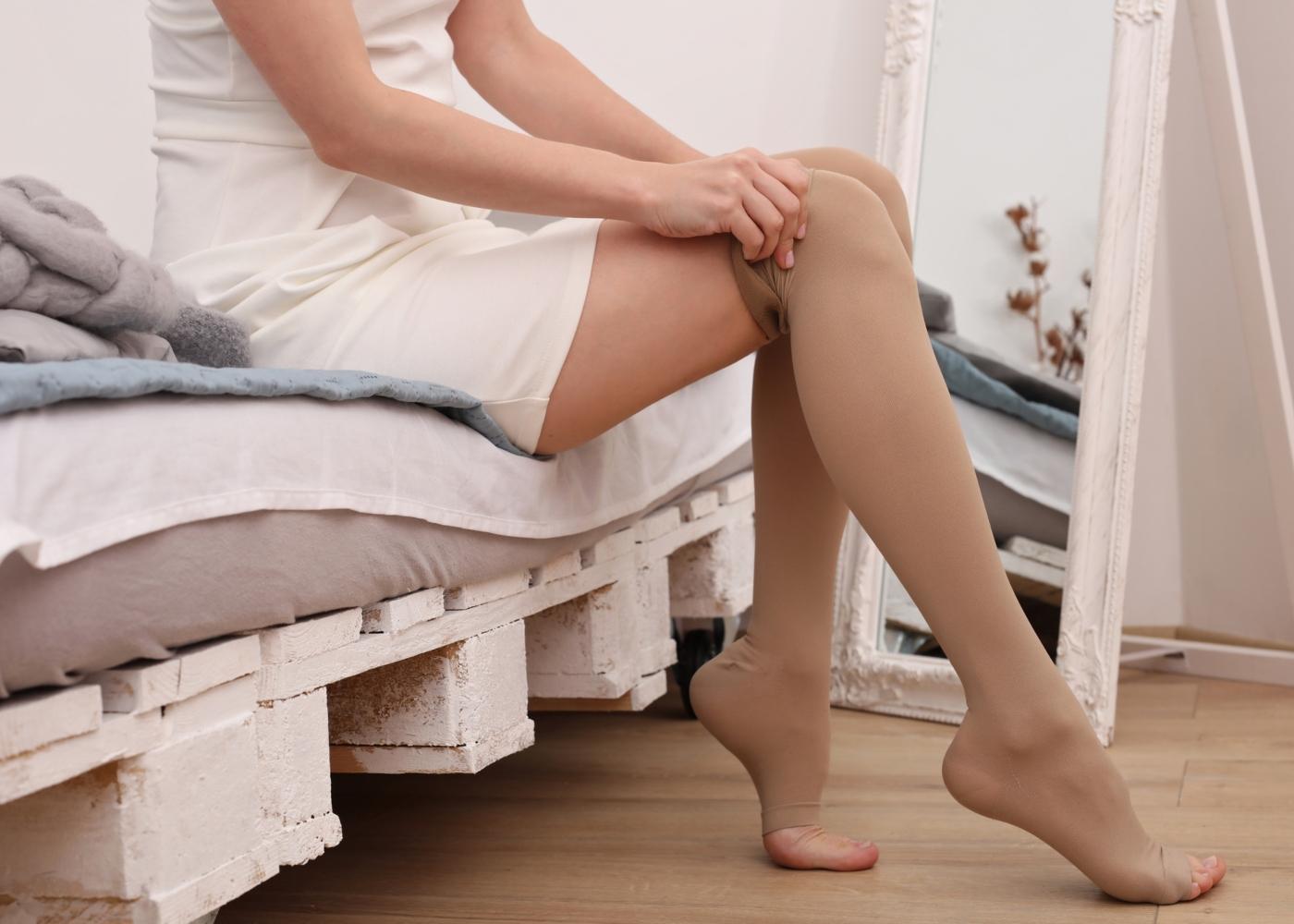 Mulher a calçar meias de compressão