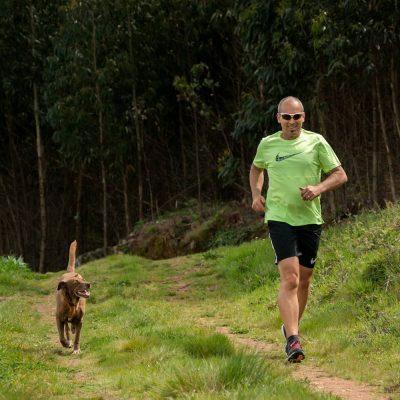homem a correr com o cão numa trilha